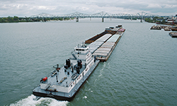 """Looking ENE from Clark Bridge Towboat """"V. W. Meythaler"""" upbound with a mixed tow including coal and scrap metal JFK and Big Four Bridges in distance At right are sand and gravel barges at Martin Marietta sand yard Twin screw towboat """"V. W. Meythaler"""" (doc. # 548689, length 145, breadth 48, GM 16-645E5 diesels, 5600 hp.) Built in 1973 by Jeffboat, Jeffersonville, Indiana Owned by American Commercial Barge Line, Jeffersonville, Indiana Sold in 1994 to UABL/Ultrapetrol, Asuncion, Paraguay, and renamed """"San Martin"""" Renamed """"Soledad"""" in 2000 Renamed """"San Martin I"""" in 2005 Photographed in late 2012 by Roberto Attias on the Paran? River at Corrientes, Argentina Current whereabouts unknown (UABL filed for bankrupcy in early 2017) Ohio River mile 604 Louisville, Kentucky Oct. 1987 File # 87j069 scanned from 35 mm Kodachrome slide"""