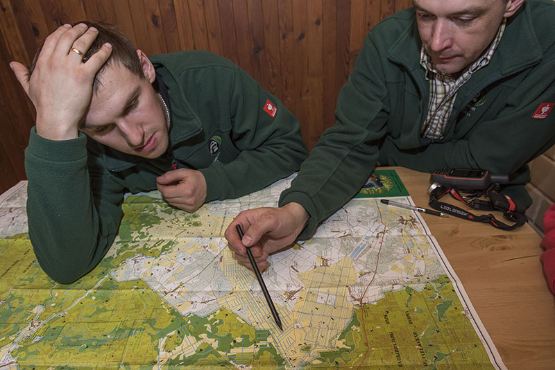 Project leader Viktar Fenchuk (right) and Aleksandr Pekach studying a map of the project area in the FZS office. Viktar is pointing to the area that will be restored wetlands. Bialowiezsa Forest, Belarus. © Daniel Rosengren